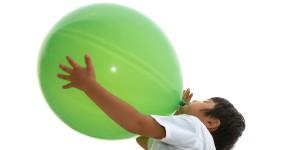 boy blowing up a big green balloon